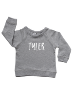 "Grey sweatshirt with the name ""Tyler"" written on it."