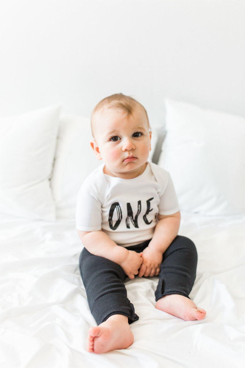 "A little boy is sitting on a bed wearing black pants and a white bodysuit that says ""one."""