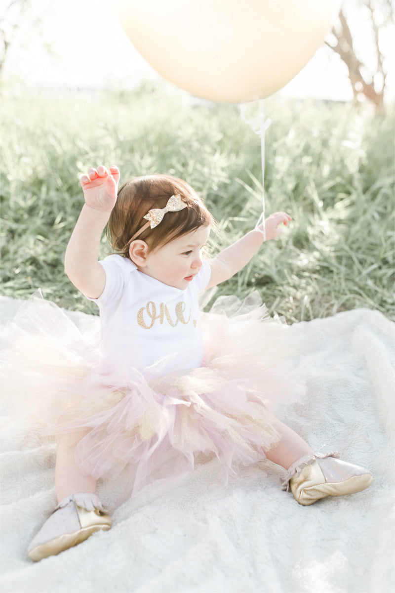 "A little girl is sitting on a blanket in a field, holding a balloon.  She is wearing a tutu and a bodysuit that says ""one."""