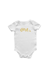 "A white bodysuit with ""one"" written on it in gold."
