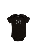 "A black bodysuit with ""one"" written on it in a marker font."