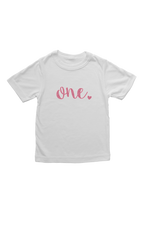 "White kids tee with ""one"" written on it in pink glitter."