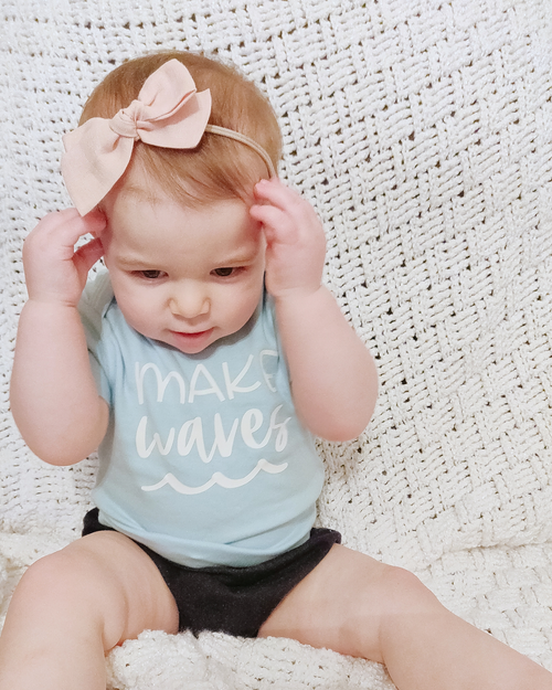 "A baby is sitting on a white blanket.  She is wearing a pink bow in her hair, and a bodysuit that says ""make waves"" and has a wave graphic on it."