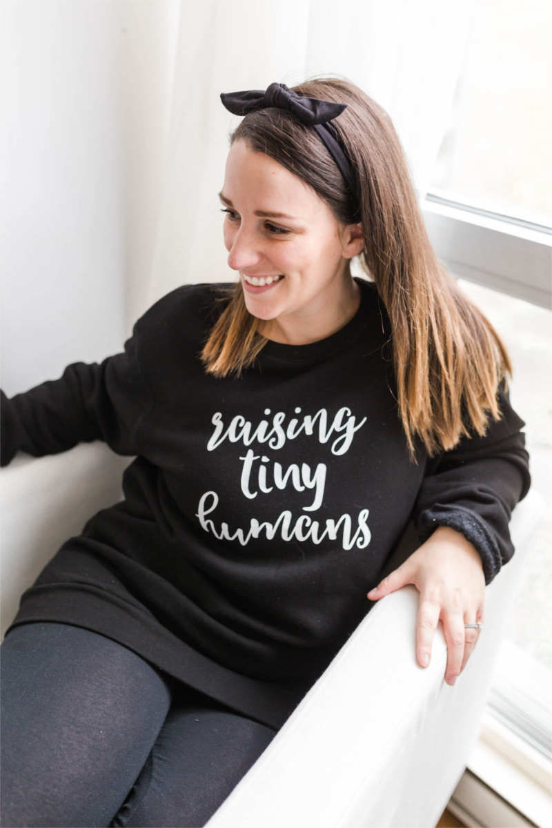 "Woman smiling while sitting in chair wearing a black ""raising tiny humans"" sweatshirt"