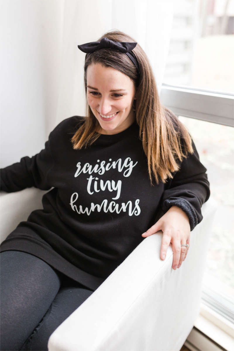 "Woman sitting in chair wearing a black ""raising tiny humans"" sweatshirt"