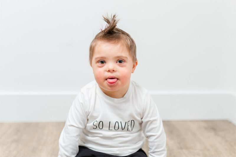"A little boy with Down's Syndrome is sitting on the floor wearing a white shirt that says ""SO LOVED"".  He has a mohawk and is sticking out his tongue."