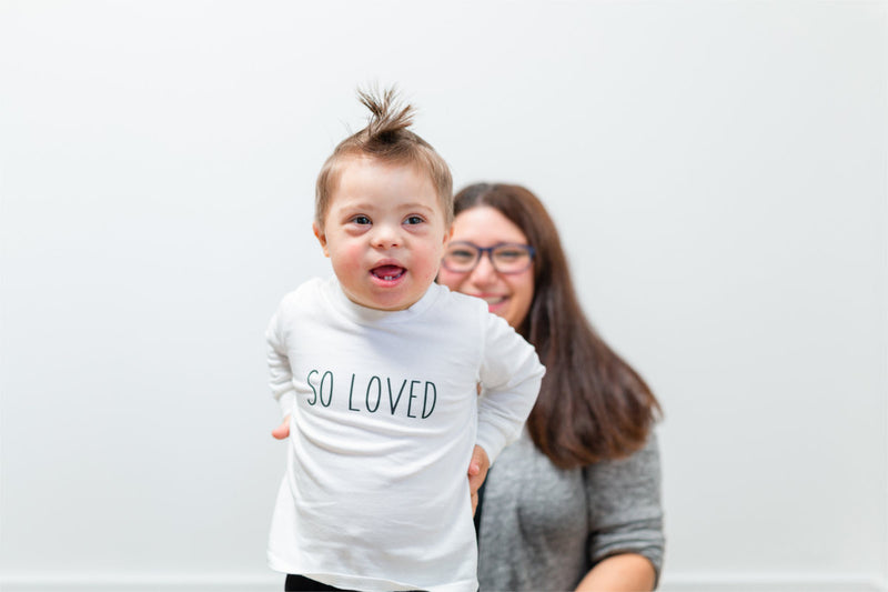 "A little boy with Down's Syndrome is wearing a white shirt that says ""SO LOVED"".  He has a mohawk and his mother is smiling behind him."