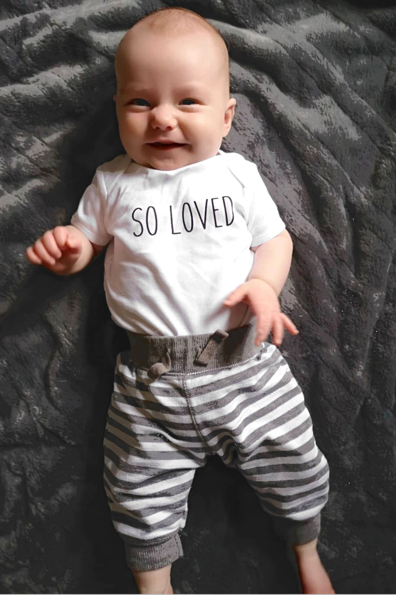 "A baby is lying on a grey blanket.  His white bodysuit reads ""so loved."""