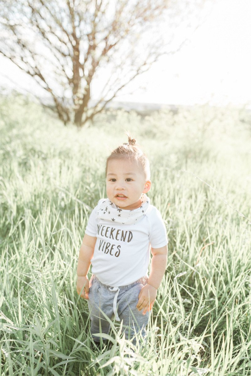 "Little boy standing in tall grass at sunset wearing track pants and a shirt that says ""weekend vibes""."