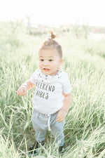 "A little boy is playing among tall grass wearing casual clothes.  His shirt reads ""weekend vibes""."