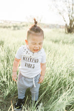 "A little boy is standing in a field of tall grass and laughing.  His shirt says ""weekend vibes""."