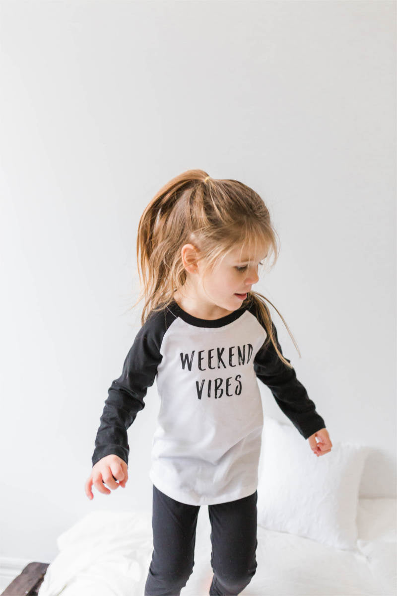 "A girl is jumping on a bed wearing a baseball tee that says ""weekend vibes."""