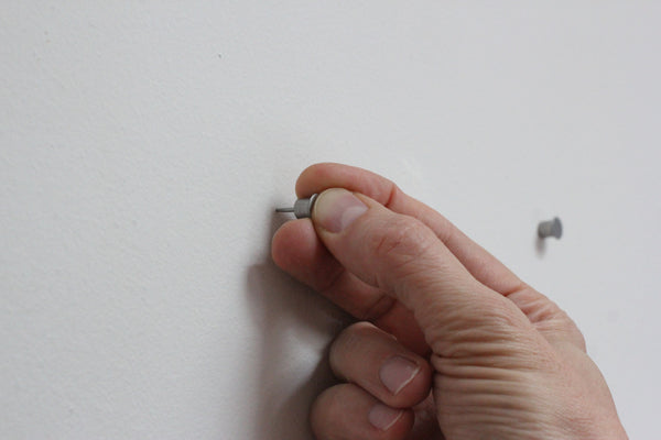 A thumb inserts the Collagewall push pin into the wall