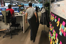 A man carries a pair of SHAY boards around the office