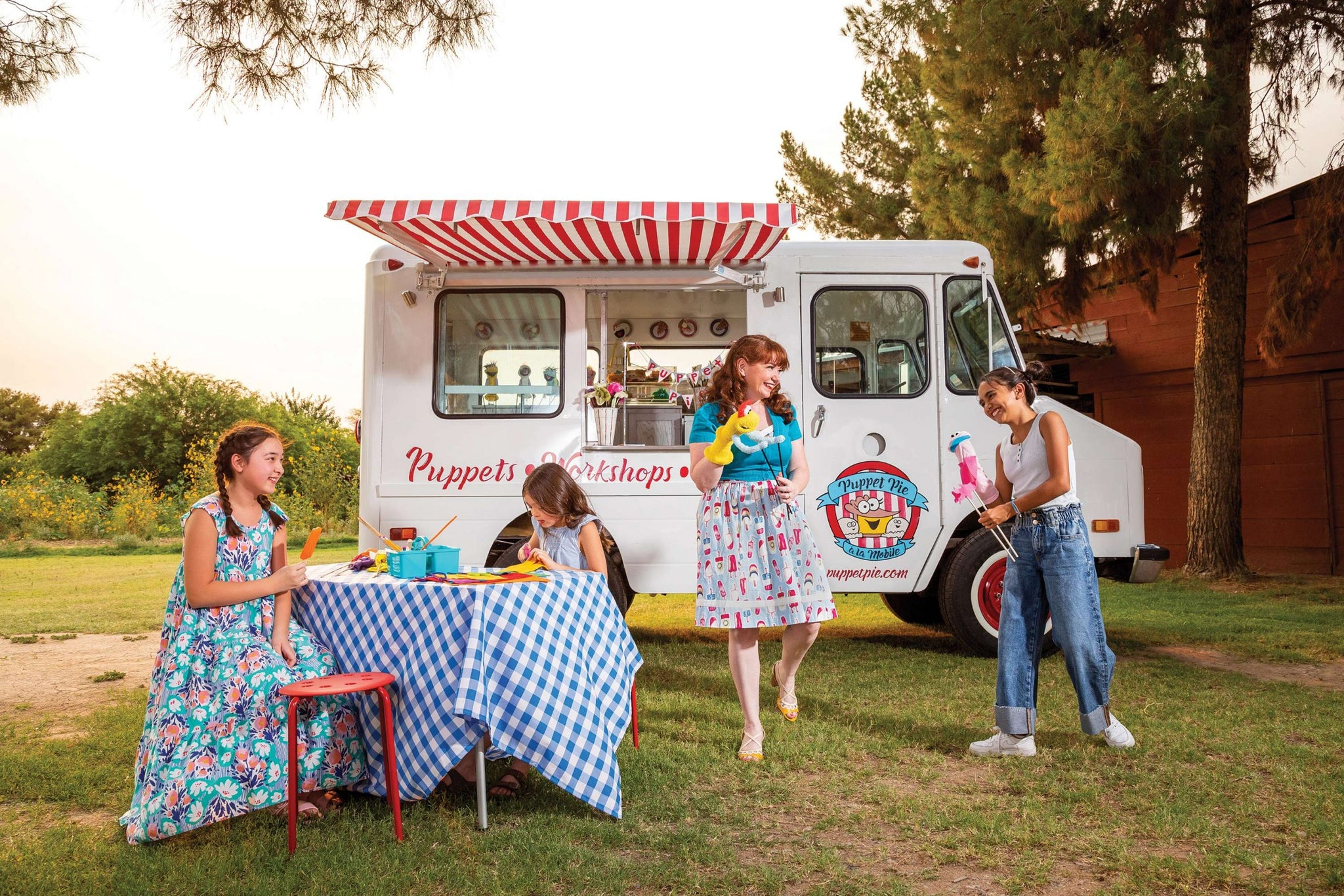 Stacey Gordon and 3 girls are in front of the puppet pie ice cream truck. The truck is white with a red awning. Two girls are sitting to the left at a table. One of them is eating an orange popsicle, the other is making a puppet. Stacey and another girl are standing to the right of the photo and laughing at a joke the girl just told with her puppet.