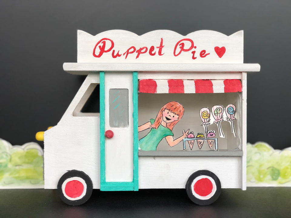 A small birdhouse painted to look like an ice cream truck. Paper puppets of stacey and ice cream puppets are inside the window. The truck is white with a red and white awning and a teal door.