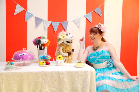 Stacey Gordon sits, donned in a frilly party dress in a chair by a table with furry puppets and tea cups and tea pots