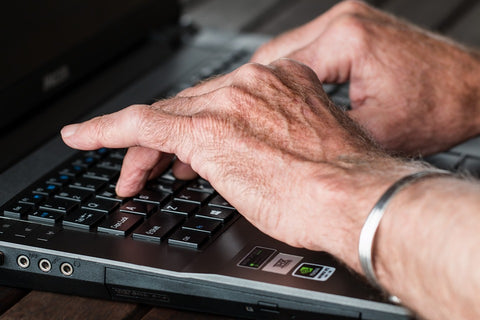 arthritis pain. image of oldhands typing on a laptop computer. wearinga  copper bracelet indicating arthritis or joint pain.