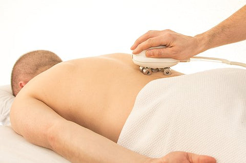 lower back pain. man lying face down ina massage table receiving a massage with a massage device.
