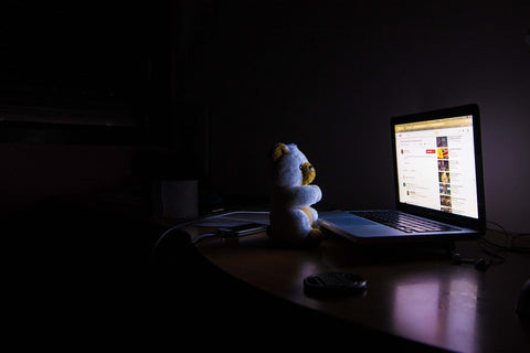 blue light effects melatonin production. teddy bear in dark with laptop open and surfing the web instaed of sleeping.