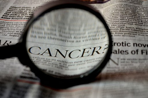 cancer pain. image of a newspaper with a magnifying glass amplifying the word cancer. The top story is about Cancer