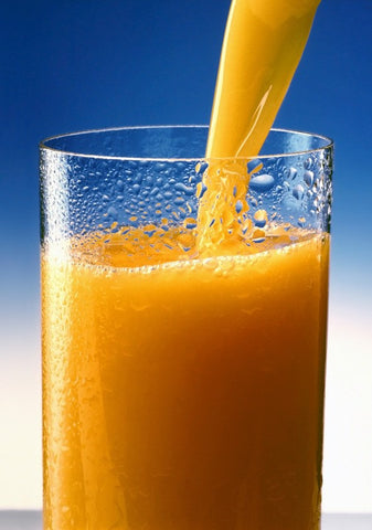 orange juiceis high in sugar and high in calories. glass of orange juice with more being poured into glass.