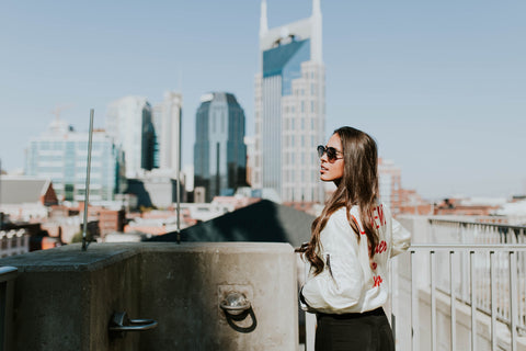 woman with long hair and white jacket wearing dark shade sunglasses on a building with a beautiful city skyline in the back