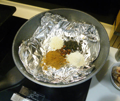 Tea spices placed on tinfoil in a pan - ToDoTea
