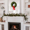 Preserved christmas Wreath with red ribbon on mirror and mantle