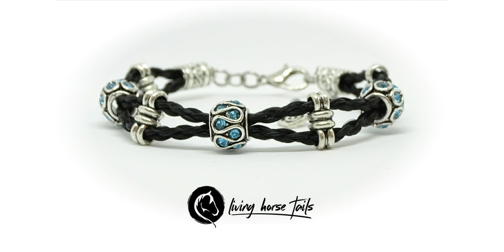 Double strand braided horsehair bracelet with blue rhinestones and silver tone beads. Front view