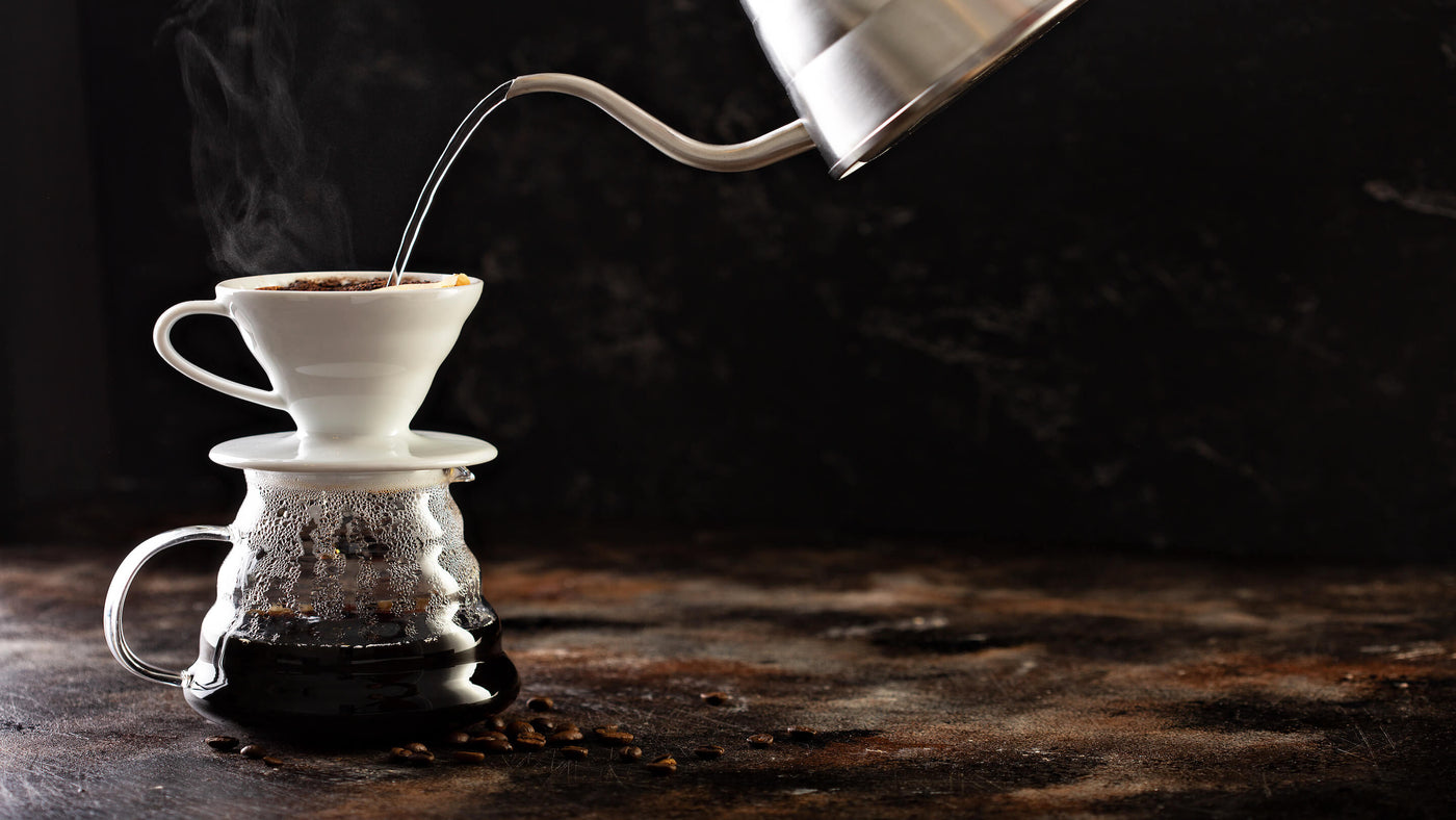 Silver kettle pouring water into coffee grounds over carafe
