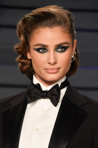 Taylor Hill in black suit with up-do and dramatic makeup