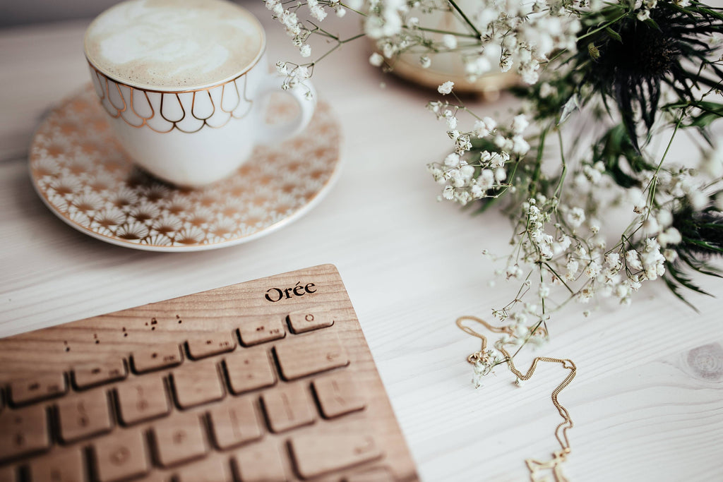 Wooden keyboard, coffee, flowers and jewellery
