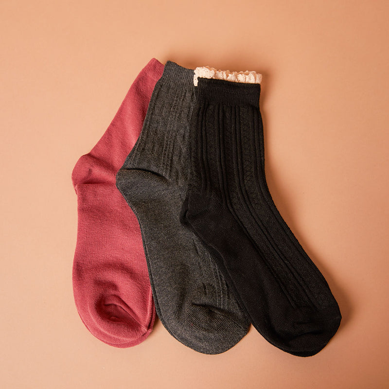 Three pack of socks in black, grey cable and burnt orange.