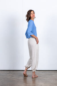 Super comfortable, relaxed linen track pant. Elasticated and drawstring waistband. Tapered cuff ideal for rolling for a cropped fit pant. Style with a plain tee. Linen rayon blend. Natural colour. Drop crotch pant. Trans seasonal pant designed in Australia. Perfect as travel pants. Sustainably driven Beach to Bar wear.