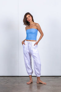 Super comfortable, relaxed linen track pant. Elasticated and drawstring waistband. Tapered cuff ideal for rolling for a cropped fit pant. Style with a plain tee. 100% linen pant. White drop-crotch track pants. Trans seasonal pant designed in Australia. Perfect as travel pants. Sustainable and ethical Beach to Bar wear.