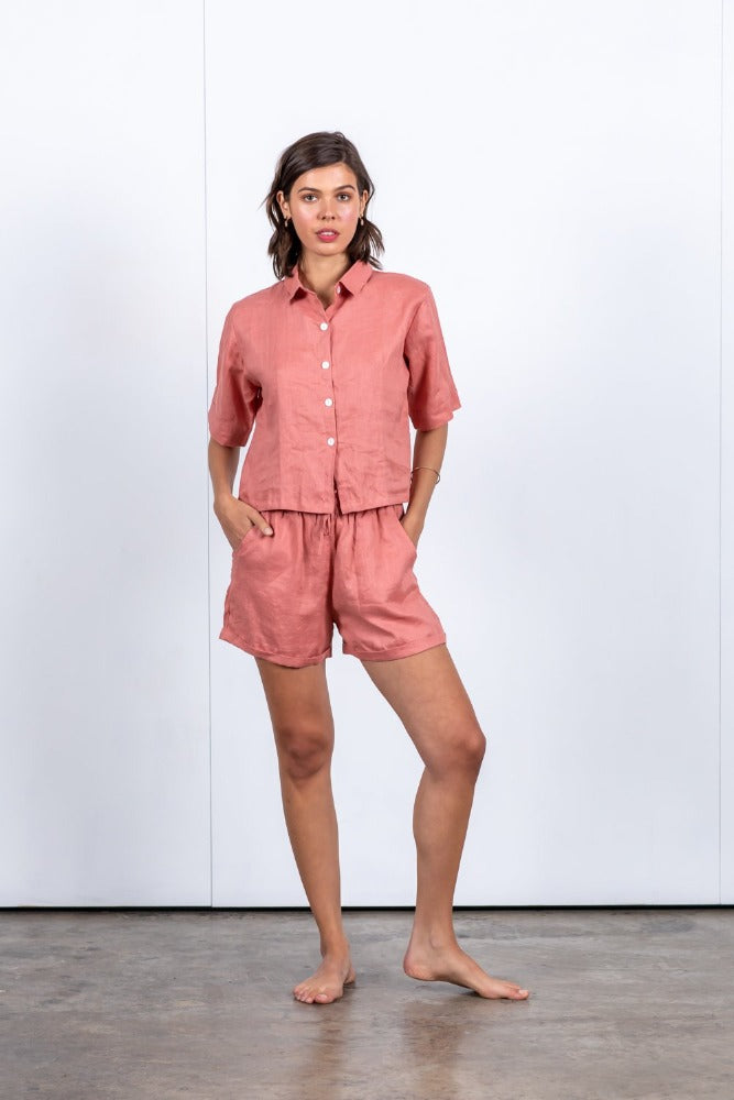 Cropped short-sleeve button-up shirt with shirt collar and wide foldable cuffs. Loose boxy fit. Hand-dyed pink linen shirt. 100% linen short sleeve shirt. Women's shirt designed in Australia. Sustainably and ethically made beach to bar wear. Comfortable and stylish women's linen shirt. Trans seasonal and versatile.