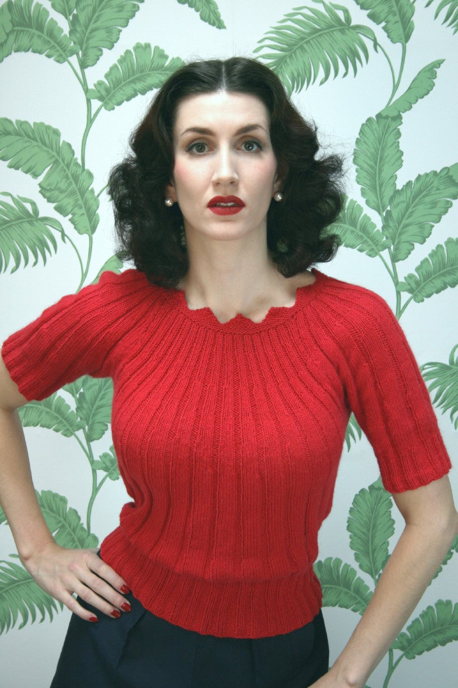 A woman wearing a red short sleeved knitted sweater