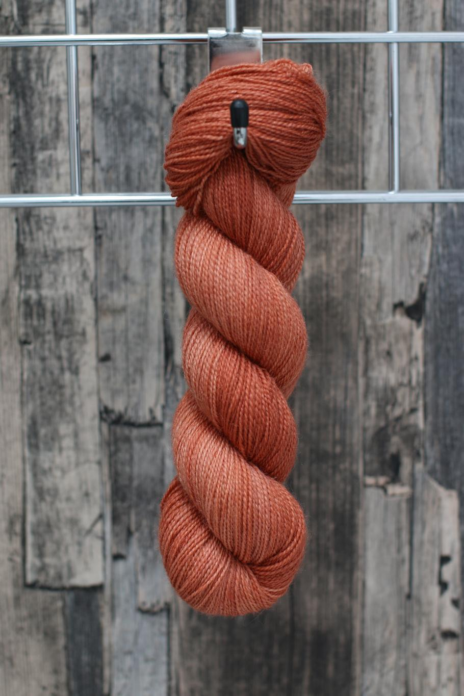 A single skein of yarn hanging from a hook in a variegated shade of soft orange