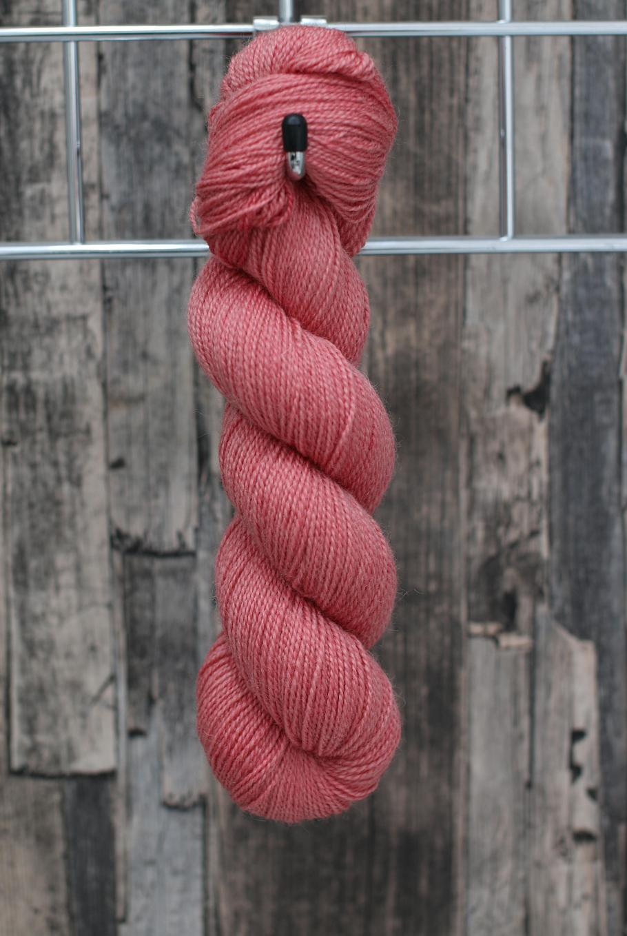 A single skein of soft but warm pink yarn, reminiscent of apple blossom