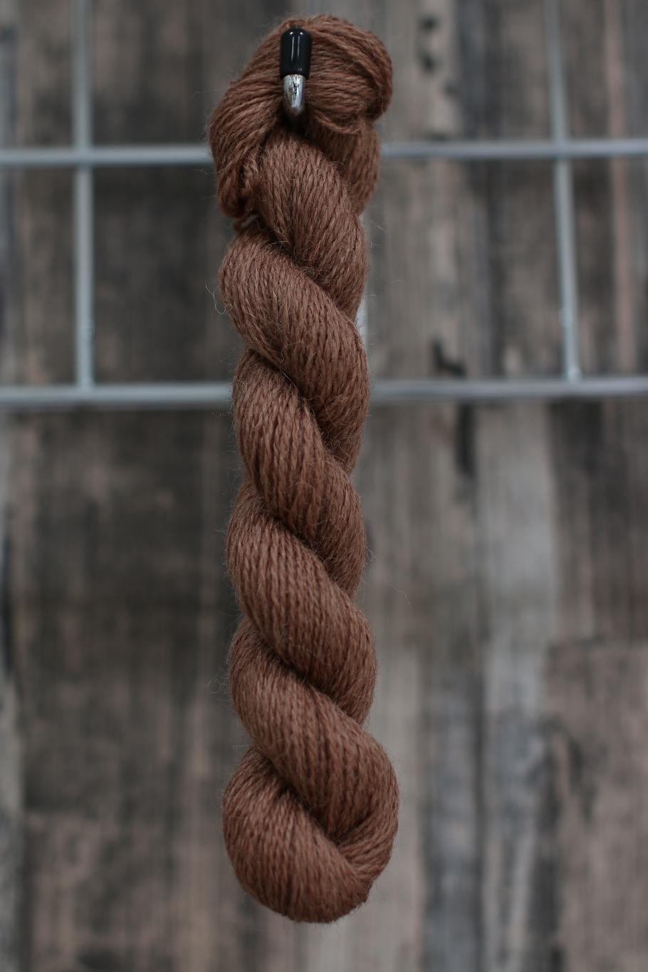 light brown skein of wool hanging from a hook