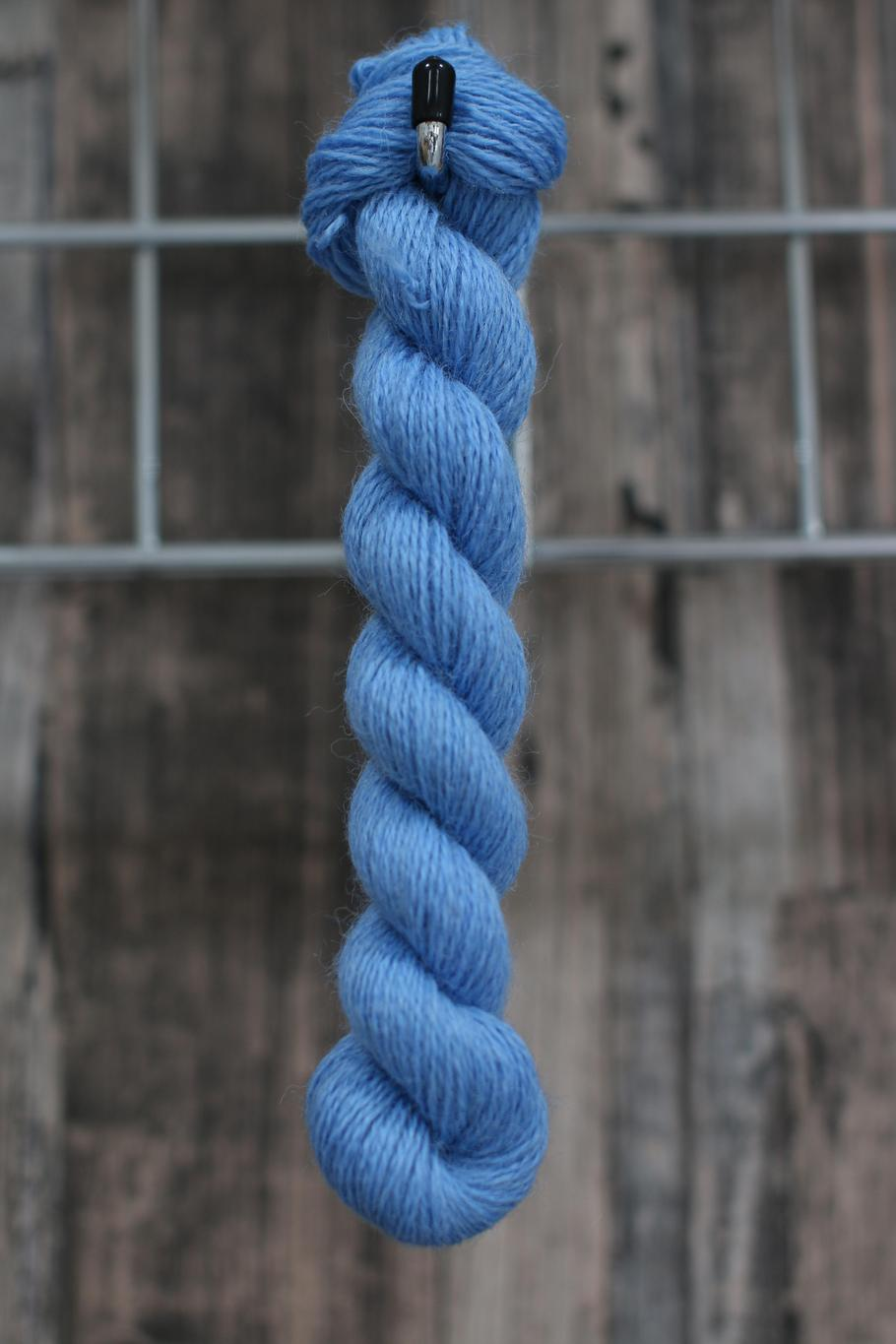 a skein of bright blue wool hanging from a hook