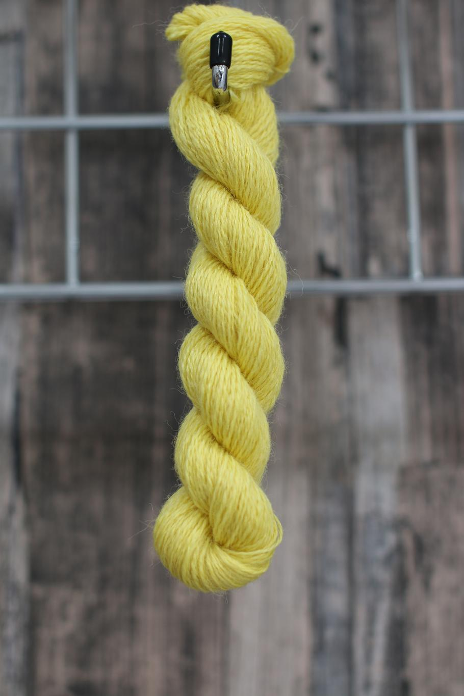 A bright lemon skein of wool hanging from a hook