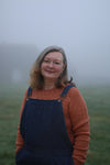 Susan standing in a misty field with hands in dungaree pockets and wearing a sweater knitted in cinnamon wool