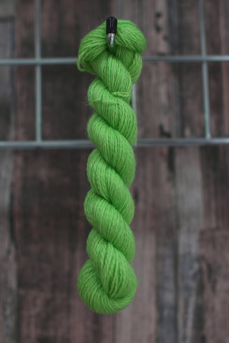 a skein of vibrant green wool hanging from a hook