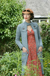 A woman stands outside among overgrown plants. She wears a natural coloured hat with a bow on top. She's wearing a long dusky pink dress with a sparkling brooch at the bust. Over this she wears a duck-egg blue knit coat with a textured pattern and pockets. The coat reaches down to about calf-length. It is open in the front and fastened with overlapping panels at the neck, held in place with large buttons.