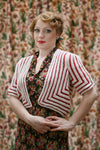 A woman with vintage styled hair stands in front of a floral curtain. She wears a black and coloured floral dress. Over the top she wears a red and white knit cardigan in a square shape with mitred corners on the cardigan fronts and on the sleeves.