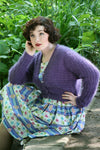 A dark haired woman sits outside on a wall with green plants behind her. She rests one elbow on her knee and her other hand is on her hip. She is wearing a vintage style dress in a blue and floral print. Over the top is is wearing a dusky lilac cardigan knit in a fuzzy angora yarn. It has a textured stitch pattern and a v neck with buttons down the front.