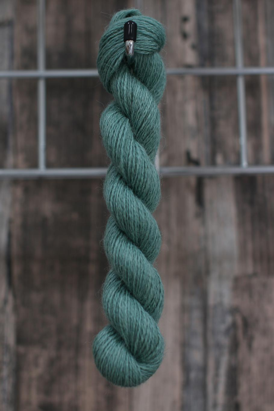 a blue-green skein of wool hanging from a hook