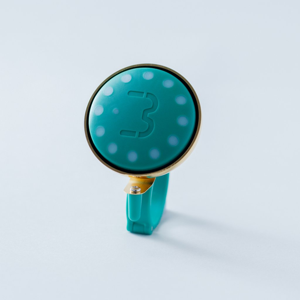 Green Blubel navigation device with a matching bell mount in gold tone